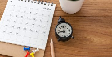 stock-photo-calendar-with-clock-and-pencil-on-wooden-table-with-space-1006044538